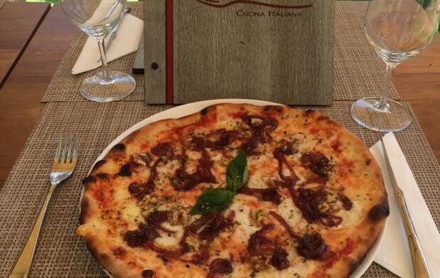 Pizza y bebida en Pizzería Capricci
